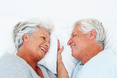 Buy stock photo Closeup of romantic senior couple relaxing in bed and smiling