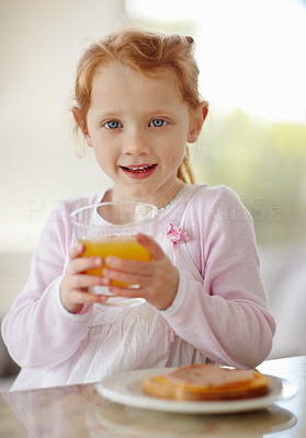 Buy stock photo Portrait of a happy adorable little girl holding a glass of juice while having breakfast