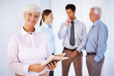 Buy stock photo Beautiful old woman holding a newspaper with group of people talking in background