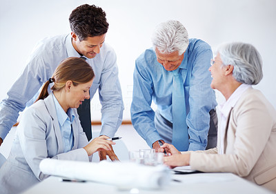 Buy stock photo Busy group of business colleagues working together on a project