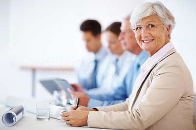 Buy stock photo Portrait of a successful old businesswoman sitting at a meeting with colleagues
