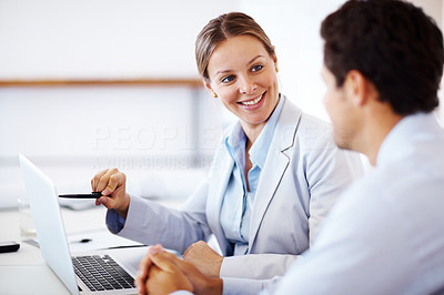 Buy stock photo Happy young businesswoman points something out to her colleague on a laptop at office