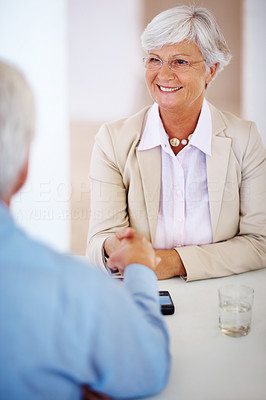 Buy stock photo Smiling mature businesswoman shaking hands with her colleague
