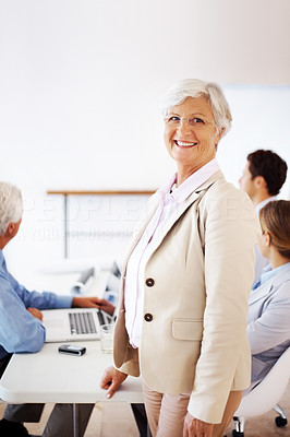 Buy stock photo Portrait of a successful old businesswoman standing with colleagues in background