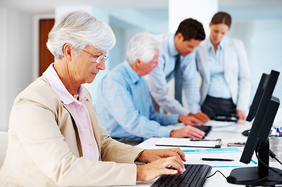 Buy stock photo Portrait of a busy old businesswoman typing on compter with her colleagues blur in background