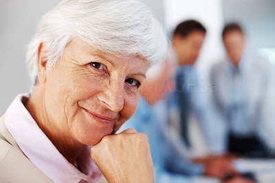 Buy stock photo Closeup portrait of a happy old businesswoman at office with colleagues blured in background