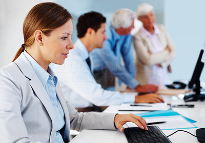 Buy stock photo Beautiful young business woman working on computer with associates in background