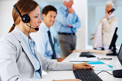 Buy stock photo Young female executive using headset and computer with colleagues in background