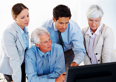 Buy stock photo Confident mature businessman sitting with his colleagues and working on computer - Teamwork
