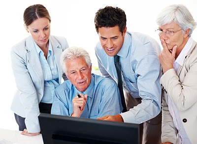 Buy stock photo Successful mature business manager working on computer with his colleagues at desk