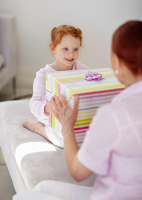 Buy stock photo Portrait of a grandmother giving present to her granddaughter