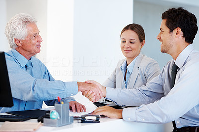 Buy stock photo Portrait of a happy young couple shaking hands with financial planner at office