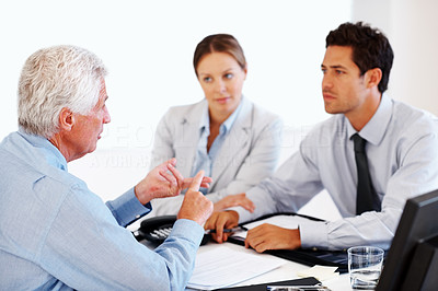 Buy stock photo Portrait of a mature advisor explaining investment plans to a young couple