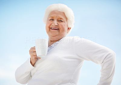 Buy stock photo Portrait of a happy senior woman drinking a cup of coffee against a blue sky