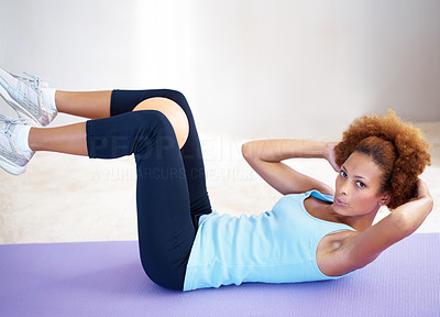 Buy stock photo Portrait of a healthy young woman lying on yoga mat doing sit ups with small ball