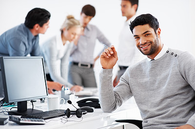 Buy stock photo Smiling business man sitting by his computer with colleagues discussing in background