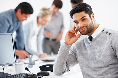 Buy stock photo Confident business man sitting in front of computer with team discussing in background