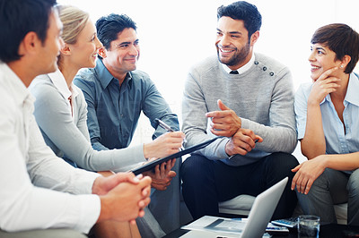Buy stock photo Smiling business people listening to their leader during meeting