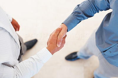 Buy stock photo Cropped image of business men shaking hands over a deal