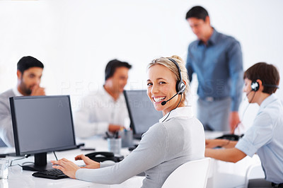 Buy stock photo Friendly customer service representative using computer with colleagues in background
