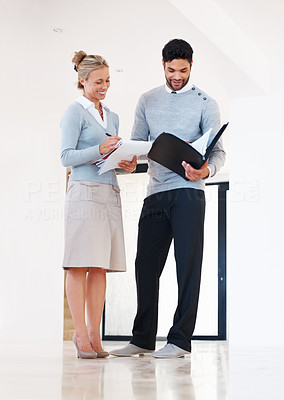Buy stock photo Full length of business man and woman standing at corridor with paperwork
