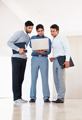 Buy stock photo Full length of professional business people discussing reports on laptop in office corridor