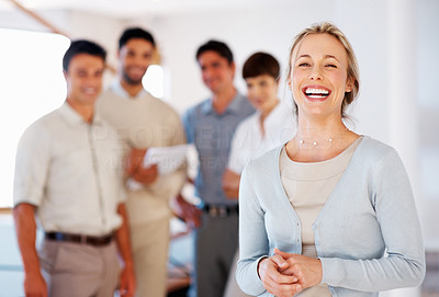 Buy stock photo Cheerful business woman with supporting team in background
