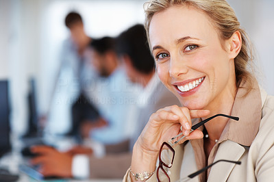 Buy stock photo Closeup of mature business woman giving you a cute smile with colleagues working in background