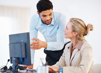 Buy stock photo Business man pointing out something important on the computer to female colleague