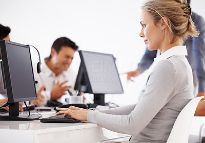 Buy stock photo Beautiful business woman working on computer with colleagues in background