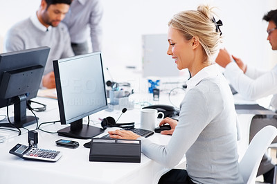 Buy stock photo Happy business woman working on computer with colleagues in background