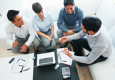 Buy stock photo High angle view of male leader discussing with his team with laptop and documents on table