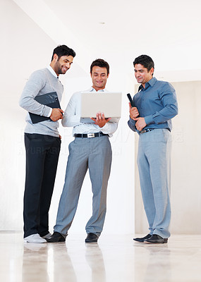 Buy stock photo Full length of three business men working on laptop in corridor