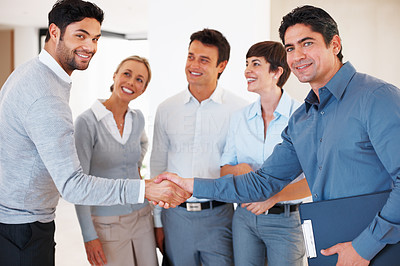 Buy stock photo Two business men greeting each other in front of colleagues