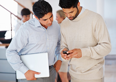 Buy stock photo Two business men reading text message on cellphone with colleagues in background
