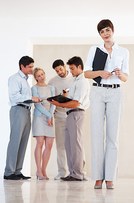 Buy stock photo Full length of successful business woman standing with colleagues discussing in background