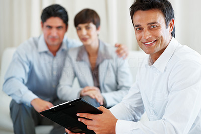 Buy stock photo Portrait of financial agent holding contract and smiling with couple sitting in background
