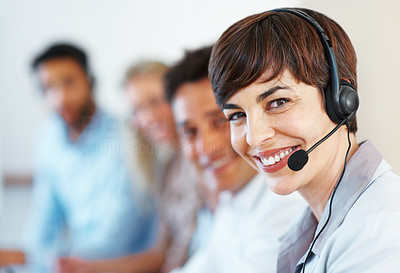 Buy stock photo Closeup of female telephone operator looking at you and smiling with colleagues in background