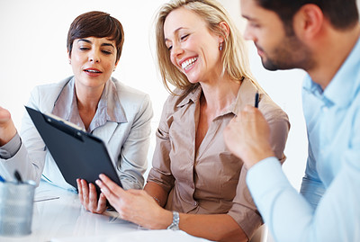 Buy stock photo Happy colleagues sitting at table and going through clipboard during business meeting