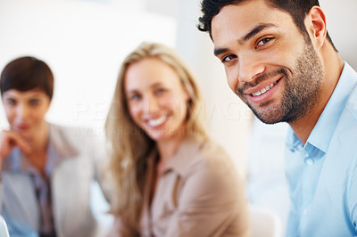 Buy stock photo Closeup of young male executive smiling with colleagues in background