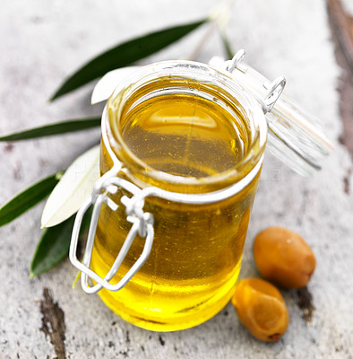 Buy stock photo Closeup of jar of olive oil and two green olives on wooden floor