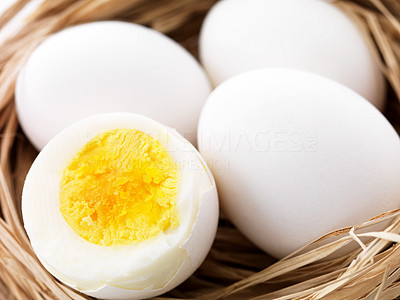 Buy stock photo Closeup One half cut boiled egg with two raw eggs in a dry nest
