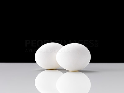 Buy stock photo Two chicken eggs on a shiny surface against black background