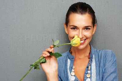Buy stock photo Portrait of pretty woman smelling yellow rose
