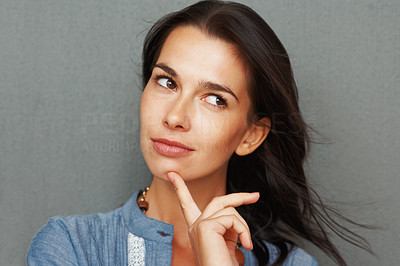 Buy stock photo Pretty woman holding finger up to chin in thought