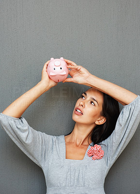 Buy stock photo Beautiful woman examining piggy bank by holding it upside down