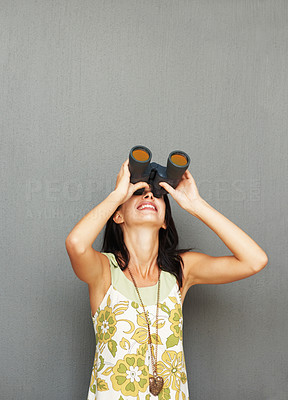 Buy stock photo Pretty woman observing something by using binoculars