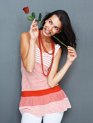 Buy stock photo Pretty woman posing with rose between teeth and looking into distance