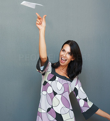 Buy stock photo Pretty young woman throwing paper airplane