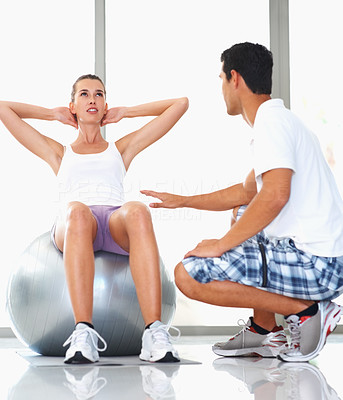 Buy stock photo Woman sitting on exercise ball assisted by personal trainer
